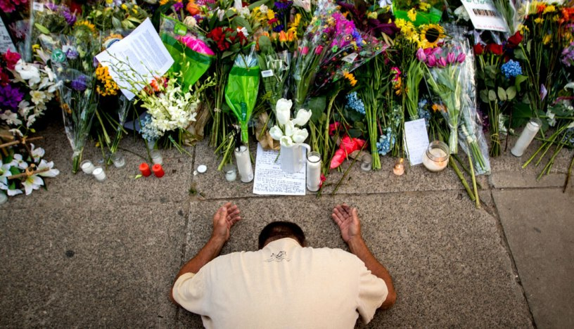 Raymond Smith of Charleston, S.C., kneels in prayer in front of the Emanuel AME Church in Charleston before a worship service / Stephen B. Morton/AP